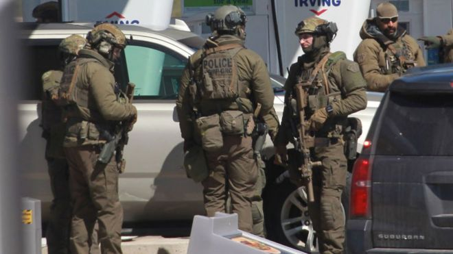 Members of the Royal Canadian Mounted Police (RCMP) tactical unit confer after the hours-long shooting rampage