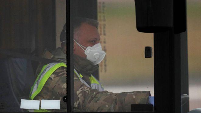 Personal de la RAF con máscara conduciendo un autobús de evacuados de China