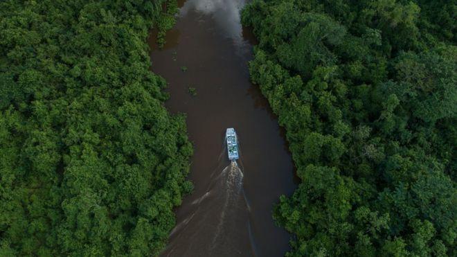 Barco navegando em rio no SESC Pantanal
