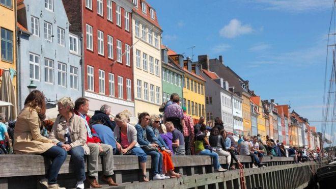 Pessoas sentadas na beira de um rio na Dinamarca