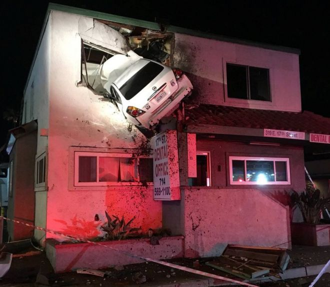 A car dangles off the upper floor of a building after hitting a road divider in California.