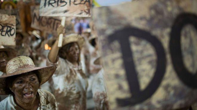 Исполнители карнавала в Рио изображают жертв грязи, держат плакаты с надписями «Смерть» и «Печаль»