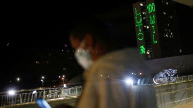 Foto à noite, mostra mulher parada em ponto de ônibus com máscara e, ao fundo, uma projeção de luz no prédio do Congresso dizendo: Luto 100 mil