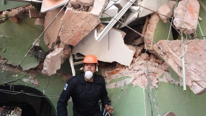 Homem de capacete e máscara anda em meio a escombros