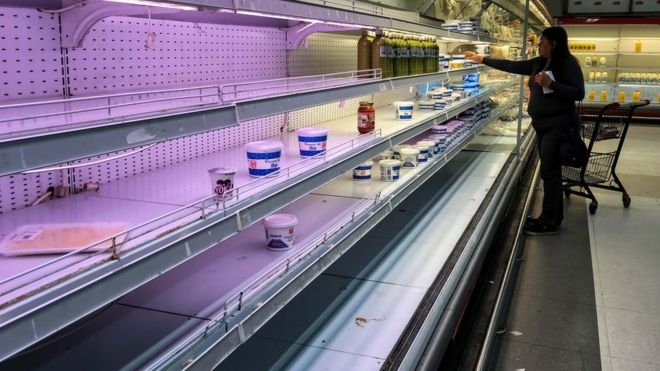 A customer looks for dairy products left in a shelf in a supermarket in Caracas, Venezuela on 27 August 2018
