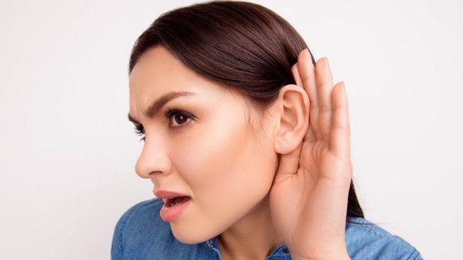 Mujer joven con mano en la oreja.