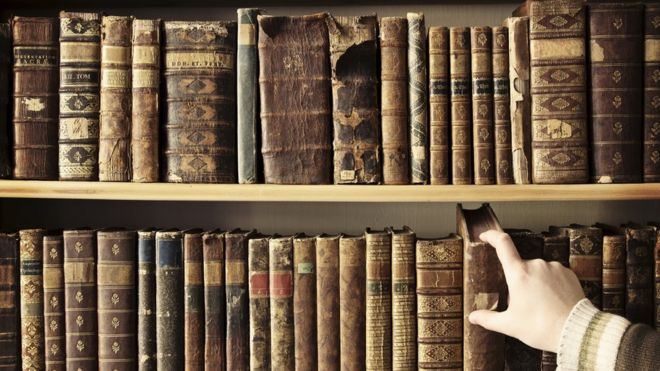 Hand reaches to shelf of second-hand books