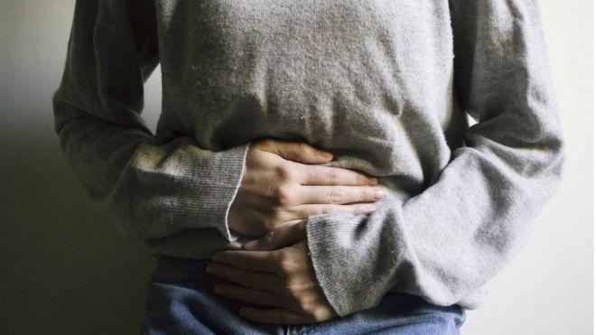 Tronco de mulher com as mãos sob o abdômen, indicando dor abdominal
