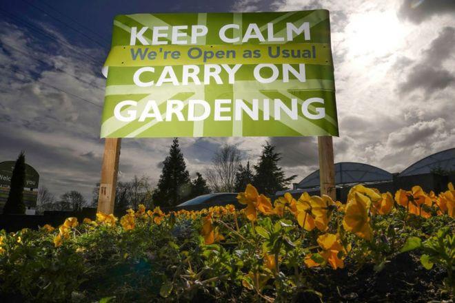 """لافتة تحث الناس على """"التحلي بالهدوء والاستمرار في العمل ببساتينهم""""، خارج مركز حديقة بورليدام في ميناء إلسمير، بإنجلترا."""