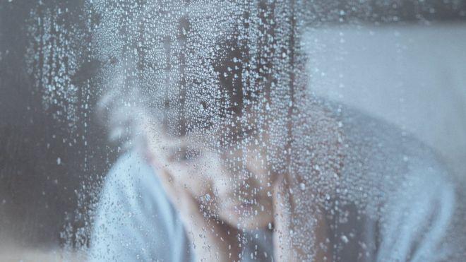 Una mujer mira a través de una ventana con lluvia