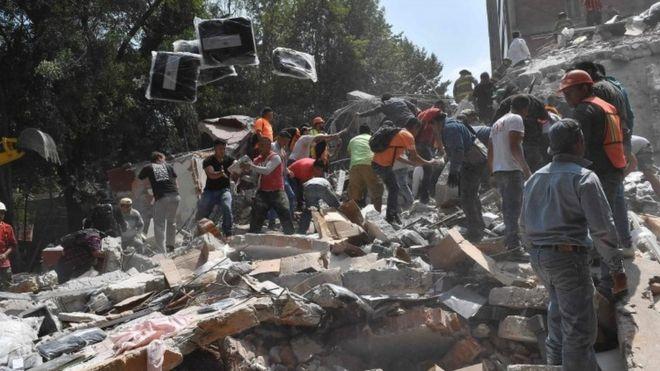 Personas recogiendo escombros de un edificio