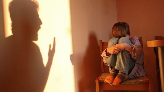 niño asustado con sombra de padre gritando