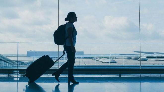 Mulher de perfil arrasta mala em aeroporto, com mochila nas costas