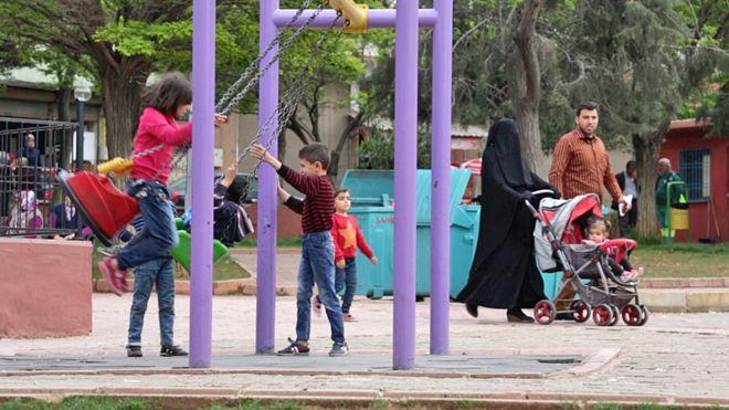 Дети играют в преимущественно сирийском районе Газиантеп, где мимо них проходит семья с матерью в черной вуали