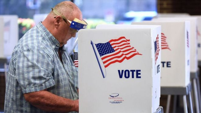 A man in a face shield casts his vote
