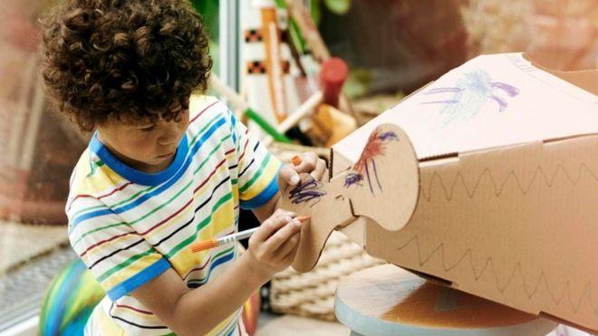 Un niño haciendo un avión de cartón