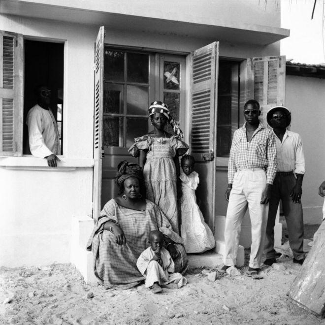 Une femme assise devant un foyer, aux côtés d'enfants et de jeunes adultes