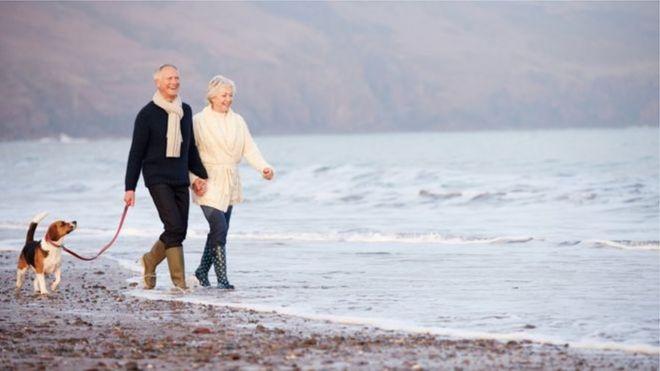 Двое пенсионеров гуляют по пляжу