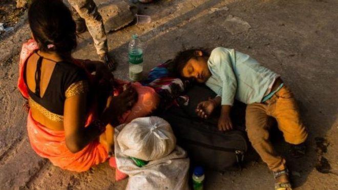 annesinin yanında yerde uyuyan bir çocuk.