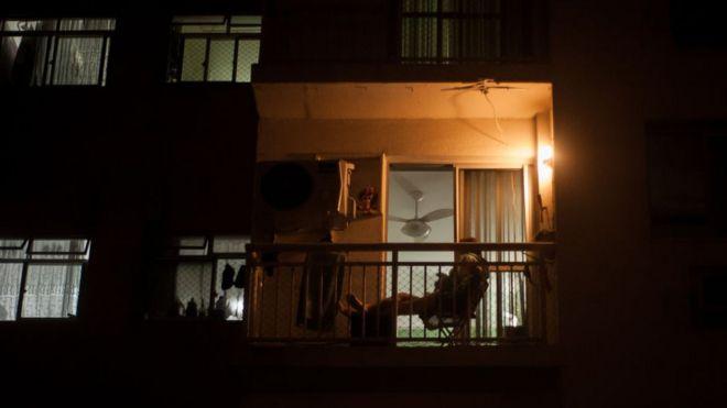 Contorno de pessoa em varanda de apartamento à noite