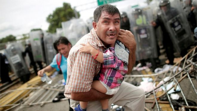 A Honduran migrant protects his child after fellow migrants, part of a caravan trying to reach the U.S., stormed a border checkpoint in Guatemala, in Ciudad Hidalgo, Mexico