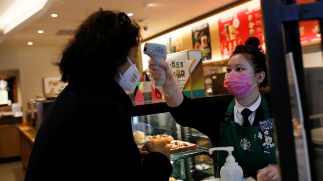 Un trabajador comprueba la temperatura de un cliente cuando ingresa a una tienda Starbucks en Beijing