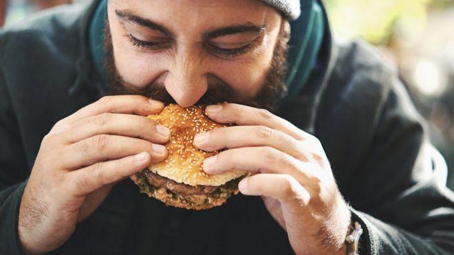 Hombre comiendo una hamburguesa