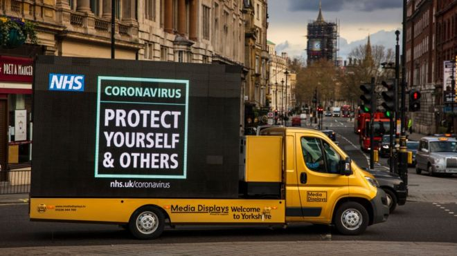 "NHS slogan ""to protect yourself and others"" written on the side of a yellow van in London"