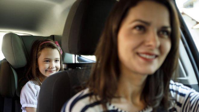 Una mujer conduciendo un auto y una niña atrás
