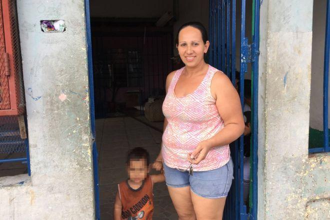 """Una costarricense posa con su hijo en la entrada de un """"peaje"""", una casa privada por la que se pasa para llegar a otro barrio y se debe pagar por el acceso."""
