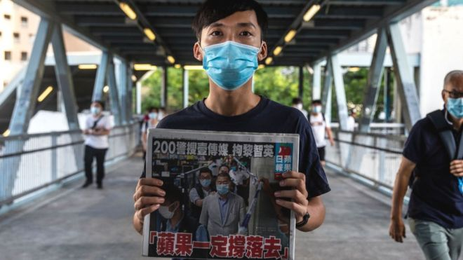 Pro-democracy district councillor Lam Chun holds a copy of the Apple Daily newspaper