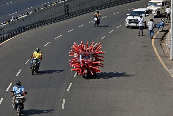 رجل يقود ريكاشة على شكل فيروس كورونا