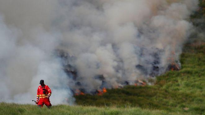 пожарный на фоне дыма