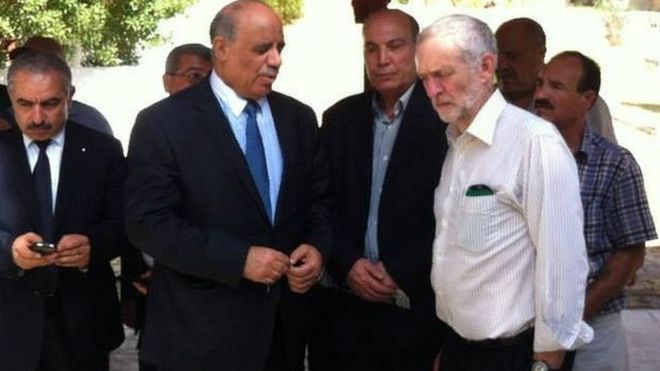 Maher Taher is pictured, centre, over Jeremy Corbyn's right shoulder at the Tunisian cemetery where the Labour leader honoured people killed in a 1985 Israeli air strike.