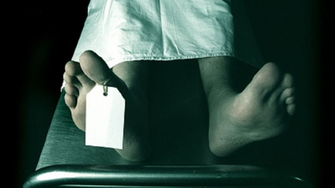 A stock image of a dead man lying on a trolley in the morgue