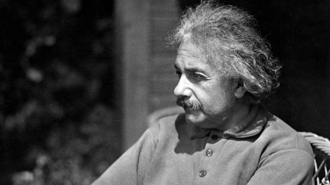 Einstein sentado, com roupa informal, olhando ao longe com semblante pensativo