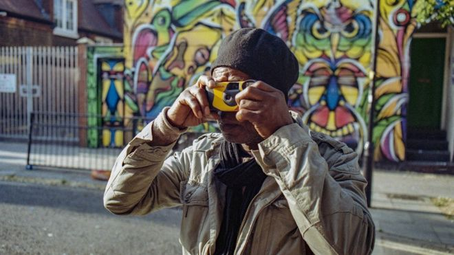 Sunny takes a photograph with a disposable camera