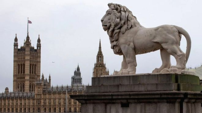 A statue of a lion stands over the River Thames from the Houses of Parliament in London, 25 October 2019