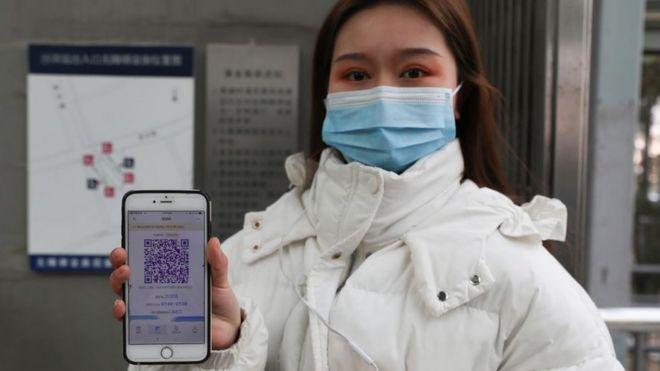 Una mujer asiática con un teléfono con un código QR.