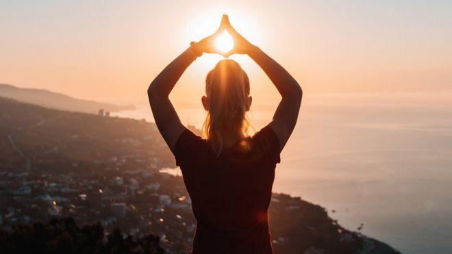 Un mujer en práctica de mindfulness con el Sol de fondo.