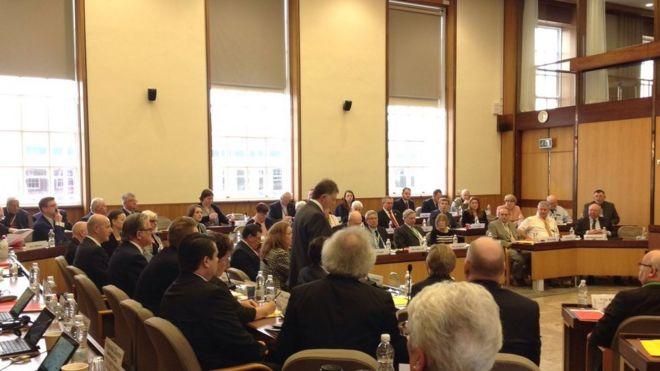 Cllr Rhodes (стоит в центре) приносит свои извинения на заседании совета