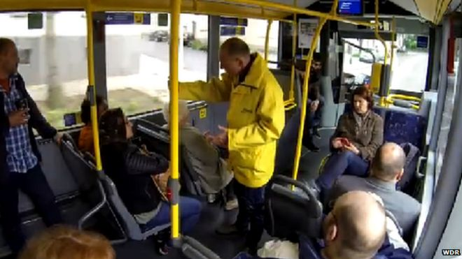 A shot from the hidden camera of the bus conductor asking two women to move