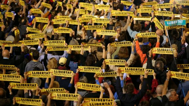 """People hold banners reading """"Freedom Political Prisoners"""" during a gathering in support of the members of the dismissed Catalan cabinet after a Spanish judge ordered the former Catalan leaders to be remanded in custody pending an investigation into Catalonia""""s independence push, outside Barcelona""""s town hall, Spain, November 3, 2017"""