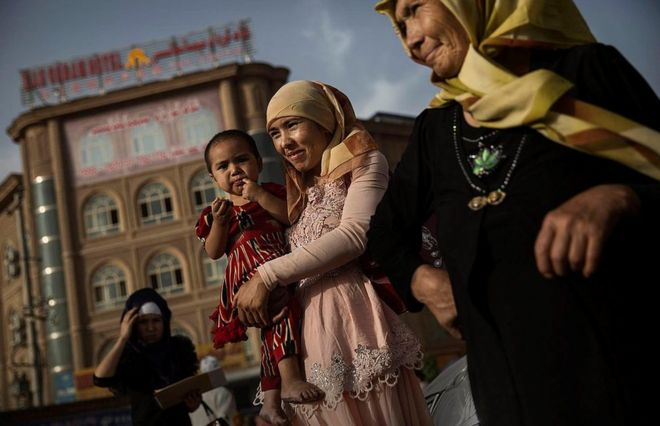 A Uyghur woman walks with her baby at a market on August 1, 2014 in old Kashgar, Xinjiang Uyghur Autonomous Region, China
