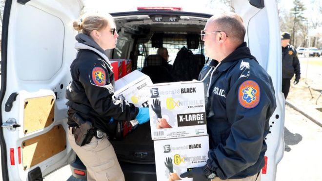 Policías cargando cajas de guantes en Nueva York
