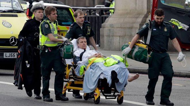 Injured officer being taken away.