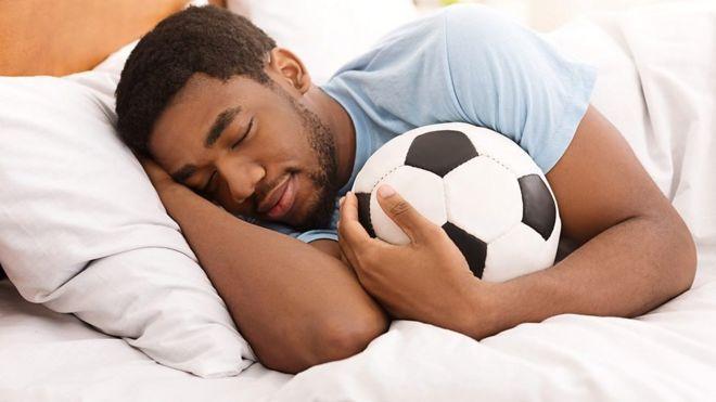 ผู้ชายนอนหลับกับลูกฟุตบอล