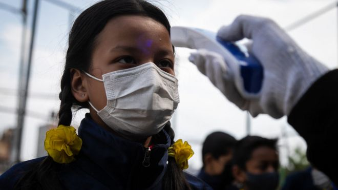 A school teacher checks the temperature of a student in Kathmandu