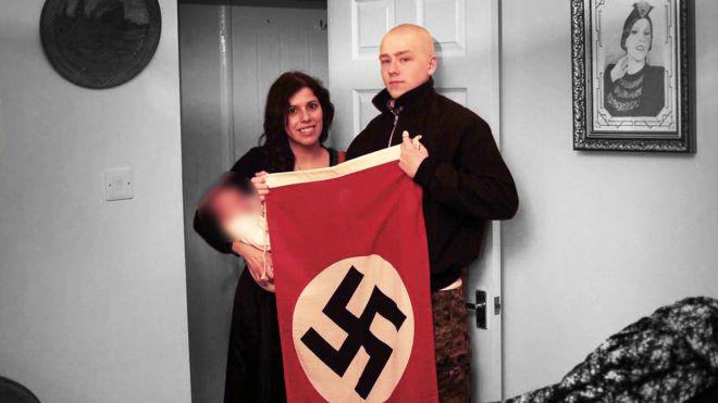 Claudia Patatas com o filho no colo ao lado de Adam Thomas, que segura uma bandeira nazista