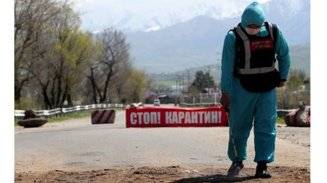 Local authorities control documents as an additional measure to prevent the spread of coronavirus disease (COVID-19) at a checkpoint in the village of Baytik, near Bishkek, Kyrgyzstan,